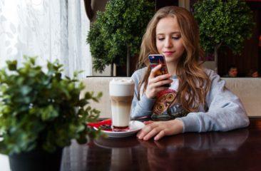 Jonge vrouw scrolt door telefoon om terras