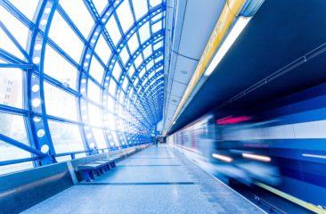 Plaatje van een rijdende trein langs een perron = platform
